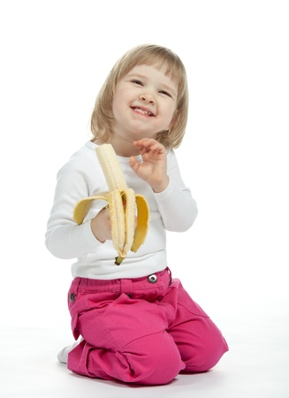 The smiling baby girl is eating ripe banana; white background