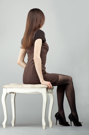 Elegant long-haired brunette girl in dress sitting on a chair, rear view; studio shot on neutral background