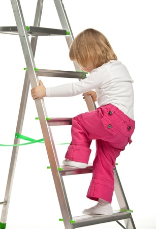 The smiling baby girl walking up the stepladder on white background