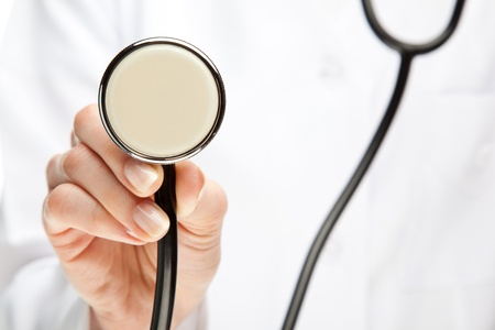 Doctor holding stethoscope; closeup of doctor's hand with stethoscope