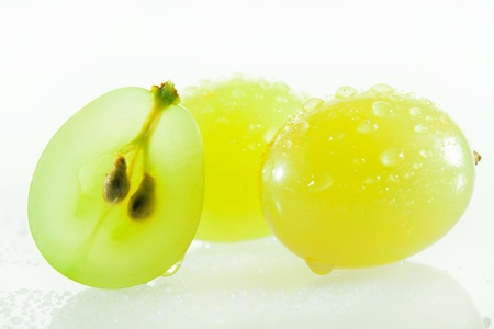 Juicy green grapes - macro shot of cut berries on white background