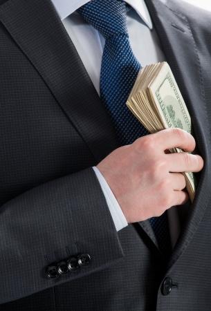 Businessman putting money in his pocket - closeup shot