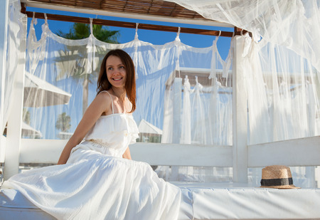 Beautiful smiling young woman sitting under white baldachin