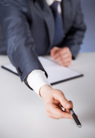 Businessman  proposing to take a pen, dark background