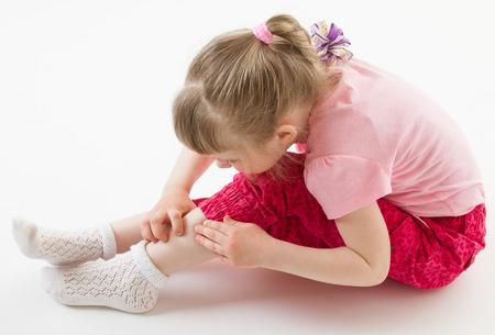 Little girl scrutinizing her leg attentively on the floor
