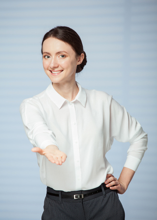 Smiling young woman  showing an empty palm, blue background
