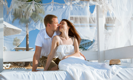 Happy young man and woman sitting under a beautiful white baldachin
