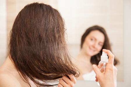 Photo pour Smiling young woman applying hair spray in front of a mirror; haircare concept - image libre de droit