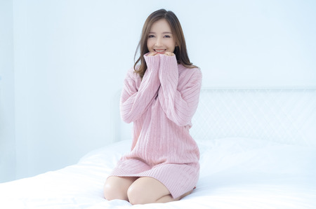 Foto de Young beautiful Asian woman in warm knitted pink clothes holding her hands underneath the chin at home. fashion model . Autumn, winter,with copy space - Imagen libre de derechos