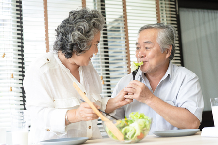 Photo pour Beautiful loving senior Asian couple eating fresh vegetable salad. Wife feeding husband and having fun at home. Looking softly on each other. - image libre de droit