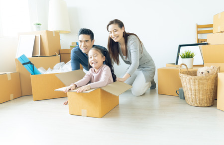 Foto de Happy young Asian family of three having fun moving with cardboard boxes in new house at moving day. Moving house day and express delivery concept. - Imagen libre de derechos