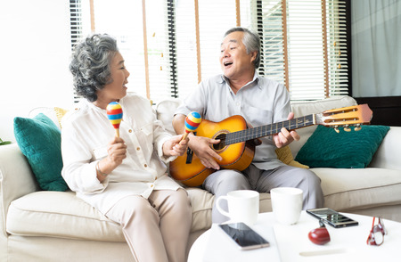 Photo pour Lovers in a living room.Funny portrait of smiling senior man playing guitar and her wife holding maracas dancing and sitting sofa at home, Activity family love and liftstyle Concept. - image libre de droit