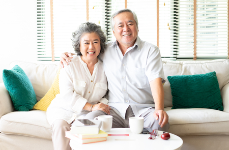 Photo pour Portrait of a Happy Asian Senior couple relaxing at home on the sofa with the wife hugging her husband  both smiling at camera - image libre de droit