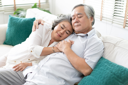 Foto de Senior couple relaxing sleeping together on sofa in living room at home. Relax and Lifestyle Concept. - Imagen libre de derechos