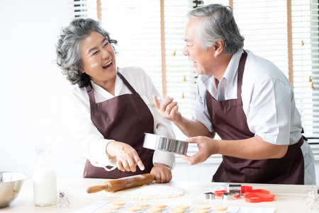 Foto de Happy family senior couple are sprinkling the dough with flour and laughing while baking cookies at home kitchen.  Baking and cooking with wife at home. - Imagen libre de derechos