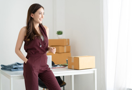 Photo for Young Asian casual woman working small business owner standing looking in distance thinking of future career opportunities and smiling at home office. Start up small business entrepreneur SME,Online selling, e-commerce, Freelance Startup Home office - Royalty Free Image