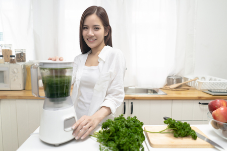Photo for Young smiling Asian woman making smoothie with fresh greens in the blender in minimalist kitchen at home and looking at camera. Healthy vegetarian smoothie for weight loss and detox. Healthy eating lifestyle concept - Royalty Free Image