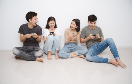 Photo pour Group of friends sitting on the floor using smart mobile phones. People addiction to new technology trends. Concept of youth, z generation, social network and friendship. - image libre de droit