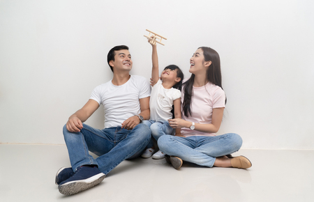 Foto de Happy multiethnic family sitting on the floor and playing toy airplane  together. Family and childhood concept. - Imagen libre de derechos