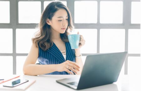 Photo for Portrait of beautiful Asian businesswoman sitting near bright window while looking at open laptop computer on table and with cup of coffee. - Royalty Free Image