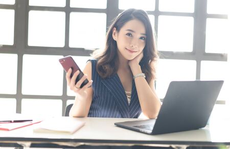Foto de Portrait of smiling pretty young Asian business woman working on laptop at office while holding mobile phone and looking at camera in the modern office. Business, technology, communication and people concept - Imagen libre de derechos