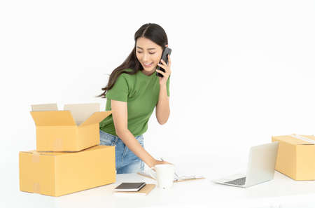 Photo pour Portrait of a pretty Asian young girl working small business talk on smartphone while check order and packing product to box in home office.Startup Small business owner, SME, Delivery Concept. - image libre de droit