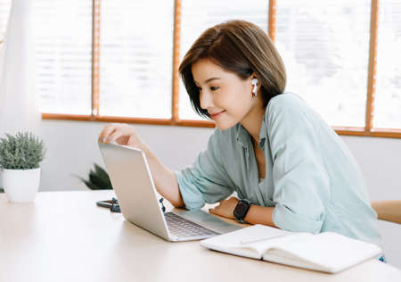 Photo pour Happy young beautiful Asian woman using laptop working remote and wireless earphones sitting at table in home office.Remote work,E learning, New normal concept. - image libre de droit