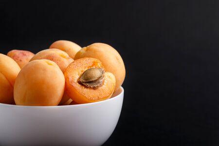 Photo pour Fresh orange apricots in white bowl on black - image libre de droit