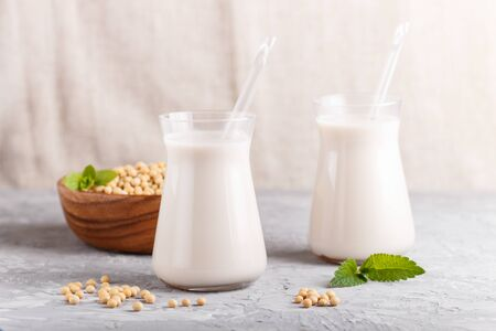 Photo pour Organic non dairy soy milk in glass and wooden plate with soybeans on a gray concrete background. Vegan healthy food concept, close up, side view. - image libre de droit