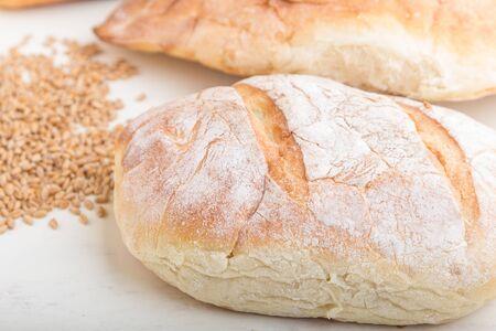 Foto für Different kinds of fresh baked bread on a white wooden background. side view, close up. - Lizenzfreies Bild