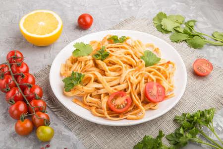 Photo pour Semolina pasta with tomato pesto sauce, orange and herbs on a white ceramic plate on a gray concrete background. Side view, close up. - image libre de droit