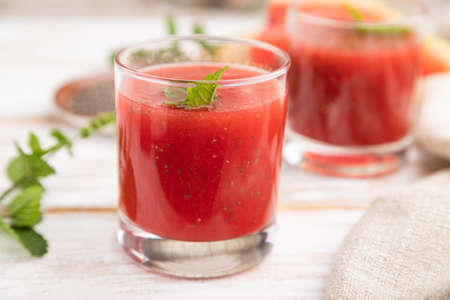 Photo pour Watermelon juice with chia seeds and mint in glass on a white wooden background with linen textile. Healthy drink concept. Side view, close up, selective focus. - image libre de droit