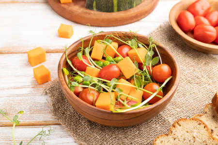 Photo for Vegetarian vegetable salad of tomatoes, pumpkin, microgreen pea sprouts on white wooden background and linen textile. Side view, close up. - Royalty Free Image