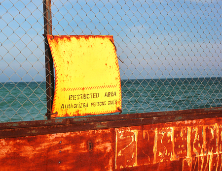 Old rusty wire fence with yellow warning sign against sea background indicating restricted area of the beach