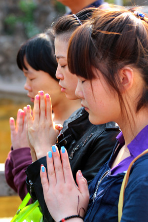 Photo pour KUNMING, CHINA - MARCH 14, 2012: Young women hold hands in anjali mudra, praying at Yuantong monastery, oldest and most famous temple in Kunming, Yunnan. - image libre de droit