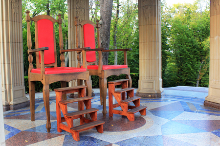 Novi Petrivtsi, Ukraine - September 22, 2017: Two giant wooden chairs with stairs in Mezhyhirya museum, the residence of Ukrainian ex-president Viktor Yanukovych.