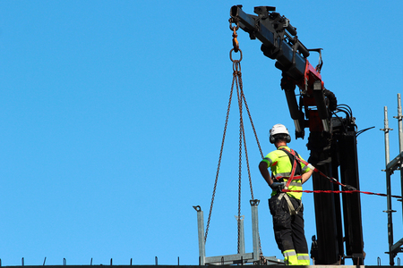 Foto de Rigger is helping the crane, keeping right balance and direction. - Imagen libre de derechos