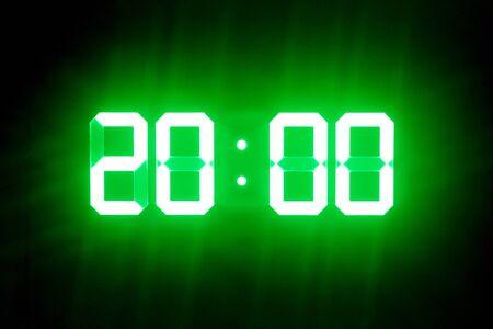 Photo pour Green glowing digital clocks in the dark show 20:00 time - image libre de droit