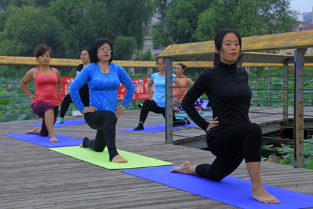 Tangshan City - September 3: women doing yoga exercise in the park, on September 3, 2016, tangshan city, hebei province, China.