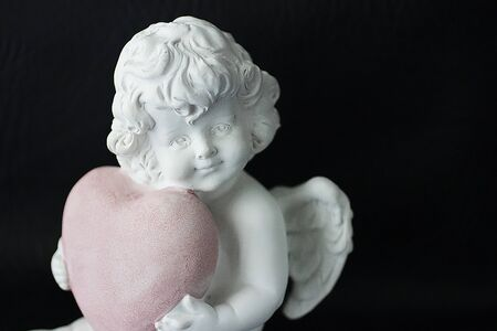 Photo for White angel with a pink heart in hands on a black background. Soft focus. - Royalty Free Image