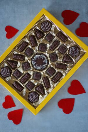 Photo pour Box of chocolates and red decorative hearts on gray background. Valentines day concept. - image libre de droit