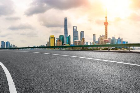 Empty asphalt road and city skyline view at sunset in Shanghai