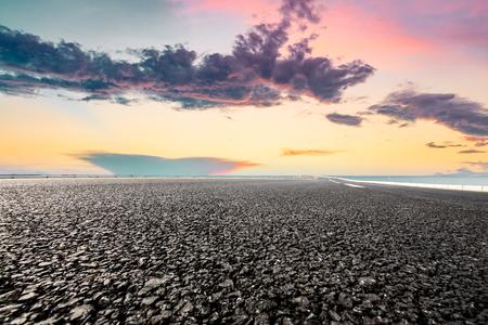 Foto de empty asphalt highway and blue sea nature landscape at sunset - Imagen libre de derechos