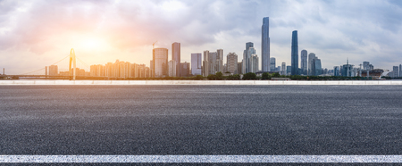 asphalt road and modern city skyline in Guangzhou at sunset,China