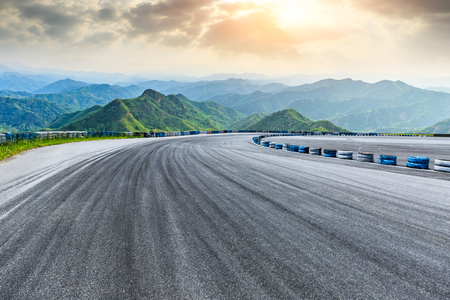 Empty asphalt square car tire brakes and mountain scenery at sunrise