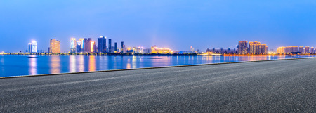 Urban asphalt road and modern buildings with river in Hangzhou at night