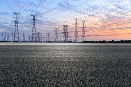 Photo pour Asphalt road and high voltage power towers at sunset - image libre de droit