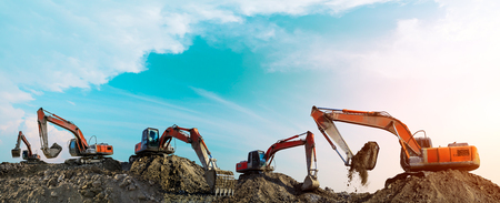 Foto de Many excavators work on construction site at sunset,panoramic view - Imagen libre de derechos