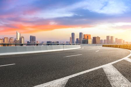 Photo pour Empty asphalt road and city skyline at sunrise in hangzhou - image libre de droit