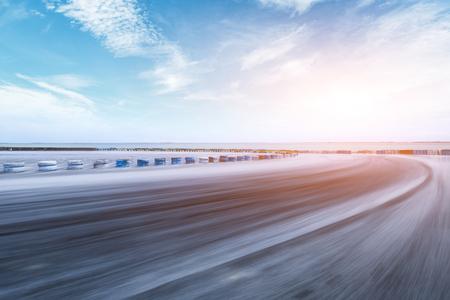 Photo pour Motion blurred asphalt race track and river with beautiful clouds at sunset - image libre de droit